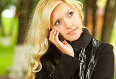 Blonde with mobile phone. Beautiful girl speaks on cellular telephone in city park Stock Photography