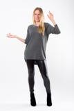 Blonde Modefrau in den dünnen schwarzen Hosen, die vor Weiß aufwerfen Lizenzfreie Stockfotos
