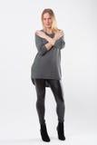 Blonde Modefrau in den dünnen schwarzen Hosen, die vor Weiß aufwerfen Lizenzfreie Stockfotografie