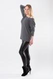 Blonde Modefrau in den dünnen schwarzen Hosen, die vor Weiß aufwerfen Stockfotografie