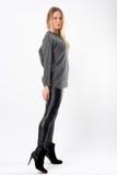 Blonde Modefrau in den dünnen schwarzen Hosen, die vor Weiß aufwerfen Stockfoto