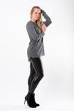 Blonde Modefrau in den dünnen schwarzen Hosen, die vor Weiß aufwerfen Stockbild