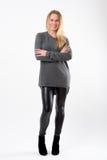 Blonde Modefrau in den dünnen schwarzen Hosen, die vor Weiß aufwerfen Stockbilder