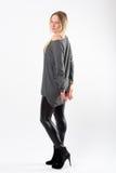 Blonde Modefrau in den dünnen schwarzen Hosen, die vor Weiß aufwerfen Lizenzfreies Stockbild