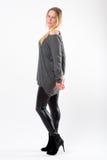Blonde Modefrau in den dünnen schwarzen Hosen, die vor Weiß aufwerfen Lizenzfreies Stockfoto