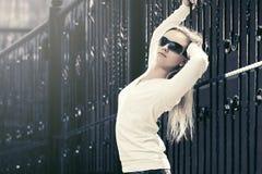 Blonde Modefrau in der Sonnenbrille nahe bei Eisenzaun Lizenzfreie Stockfotos