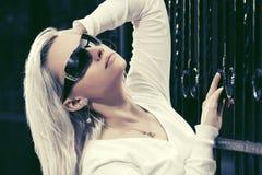 Blonde Modefrau in der Sonnenbrille nahe bei Eisenzaun Lizenzfreies Stockbild