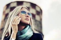 Blonde Modefrau, die um den Handy ersucht Lizenzfreie Stockbilder