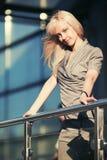 Blonde Modefrau gegen Fenster eines Malls Lizenzfreie Stockfotografie