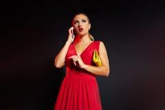 Blonde Modefrau im roten Unterhaltungssmartphone Lizenzfreie Stockfotografie