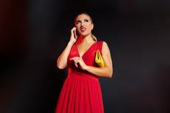 Blonde Modefrau im roten Unterhaltungssmartphone Stockfotos