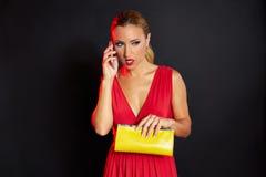 Blonde Modefrau im roten Unterhaltungssmartphone Stockbilder