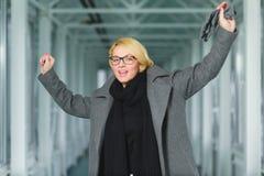 Blonde Modefrau kleidete Mantelstand in der Lobby Stockbilder