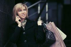 Blonde Modefrau mit Einkaufstaschen um Handy ersuchend Lizenzfreies Stockbild