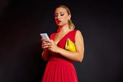 Blonde Modefrau in rotem Schreiben Smartphone Lizenzfreies Stockbild
