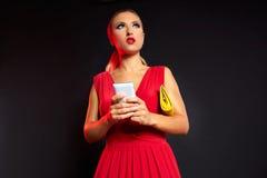 Blonde Modefrau in rotem Schreiben Smartphone Stockfoto