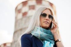 Blonde ModeGeschäftsfrau, die um den Handy im Freien ersucht Lizenzfreie Stockfotografie