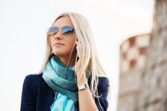 Blonde ModeGeschäftsfrau, die um den Handy im Freien ersucht Stockbilder