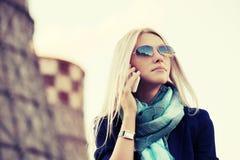 Blonde ModeGeschäftsfrau, die um den Handy im Freien ersucht Stockfotografie