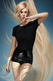 Blonde model in a black blouse and latex shorts Stock Photos