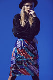 Blonde model in black hat, top and multi skirt Stock Photo