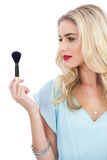 Blonde model in blue dress looking at her blush brush Stock Photography