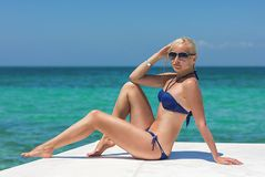 Blonde model on the boat deck posing in sunglasses. Ocean background royalty free stock photo