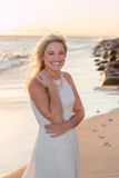 Blonde model with dress at the beach. Standing and smiling royalty free stock photos