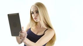 Blonde model girl doing selfie on your gadget. White studio stock footage