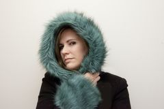 Cheeky woman smirking in fur coat royalty free stock images