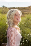 Blonde model laughing. Blonde model standing in field and laughing stock photo
