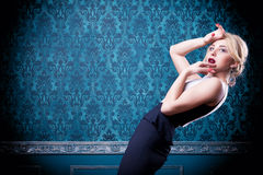 Blonde model posing in blue vintage room. Beautiful blonde model posing in blue vintage room. Rococo interior. Professional make up and studio lighting. Luxury Stock Images