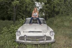Blonde Model Posing With A Vintage Car Stock Image