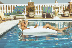 Blonde model relaxing in pool Stock Photo