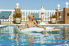 Blonde model relaxing in pool Royalty Free Stock Photo
