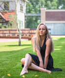 Blonde model sitting on the grass. Blonde model in Black long dress sitting on the grass Royalty Free Stock Photos