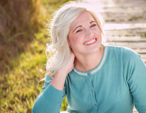 Blonde model sitting outdoors portrait. Blonde model sitting down smiling close up with blurred background stock photography