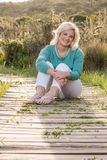 Blonde model sitting outdoors portrait. Blonde model sitting down on walkway holding legs and smiling royalty free stock photos