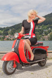 Blonde Model in a summer dress on a scooter Royalty Free Stock Photos