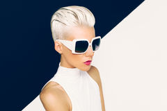 Blonde model in trendy sunglasses with stylish Haircut. Fashion Stock Photography