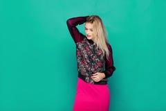 Blonde moderne Frau auf grünem Hintergrund Stockfotografie