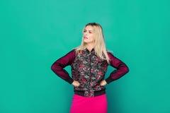Blonde moderne Frau auf grünem Hintergrund Stockbild