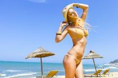 Blonde moderne Frau, die in einem goldenen Bikini aufwirft Lizenzfreie Stockbilder