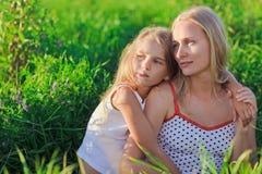 Blonde moeder en dochterzitting op groen gras Royalty-vrije Stock Foto's