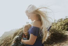 Blonde mom with her son outdoors stock image