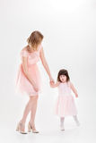 Blonde mom holding the hand of sweet little daughter in pink dre Royalty Free Stock Photo