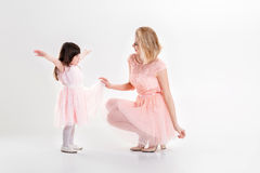 Blonde mom and sweet little daughter in pink dresses princesses Stock Image