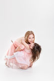 Blonde mom and sweet little daughter in pink dresses princesses Royalty Free Stock Images