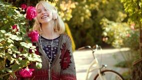 Blonde mooie vrouw die aan muziek op een weide luisteren De herfstvrouw met herfststemming Hello-de de Herfst tot ziens Zomer Het stock video