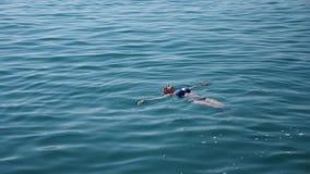 Blonde mooie vrouw die van het water in de open zee, het drijven genieten Mening van hierboven Langzame Motie stock videobeelden